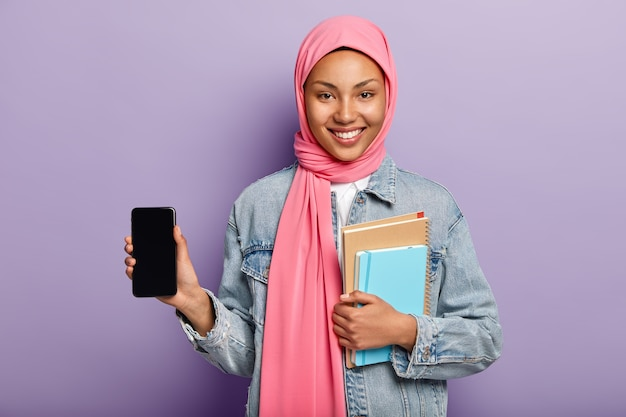 Satisfied charming young muslim woman in pink hijab on head Free Photo