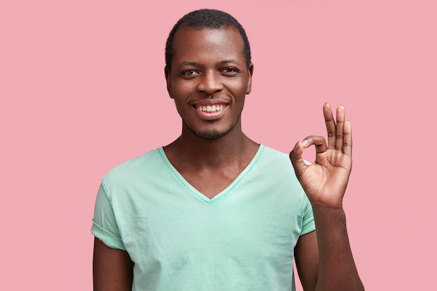 Soddisfatto maschio dalla pelle scura con felice espressione, gesti con la mano come mostra segno ok, dimostra che tutto va bene, mostra approvazione, isolato su rosa Foto Gratuite