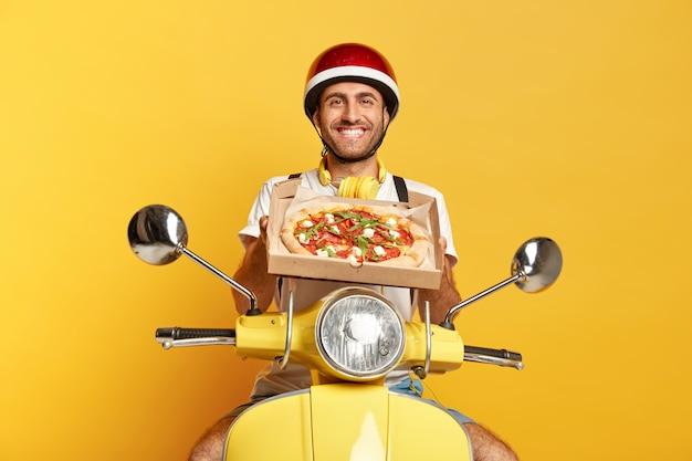 ピザの箱を持っている間黄色いスクーターを運転するヘルメットで満足している配達員 無料写真
