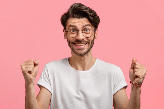 Удовлетворенный эмоциональный небритый мужчина с модной стрижкой, густой щетиной, с успехом и победой сжимающий кулаки, в белой футболке и очках, изолирован над розовым пространством Бесплатные Фотографии