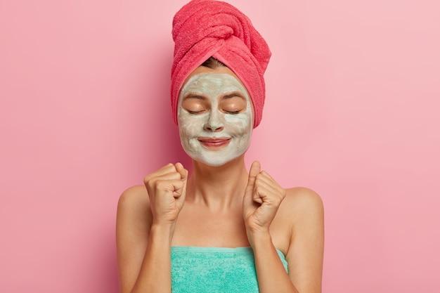 満足している女性モデルは、喜んで拳を食いしばり、定期的にシャワーやバスマスクを浴びた後、タオルで包んだフェイシャルマスクの助けを借りて血行を刺激します。 無料写真
