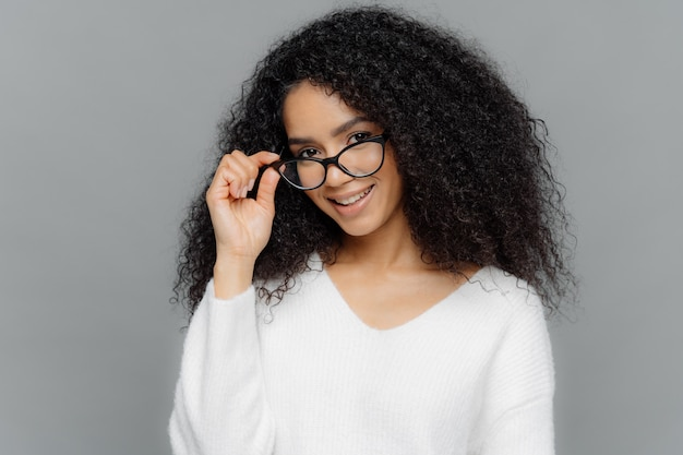 Satisfied female teacher keeps hand on frame of glasses, smiles happily Premium Photo