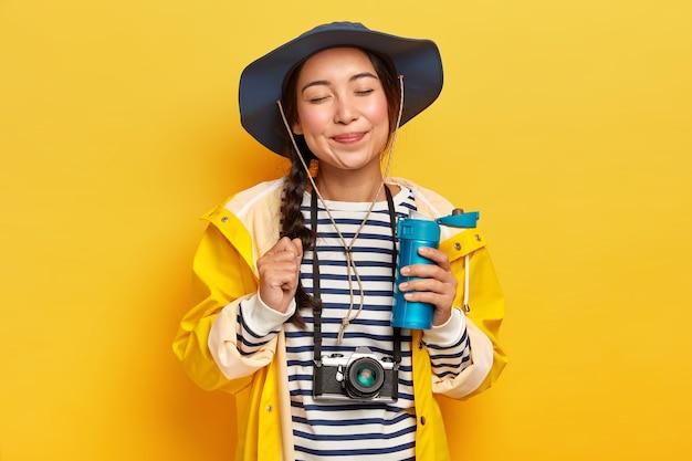Viaggiatore soddisfatto con aspetto asiatico, indossa cappello, maglione a righe e impermeabile, retro macchina fotografica sul collo, tiene la bottiglia di bevanda calda, isolato sopra il muro giallo Foto Gratuite