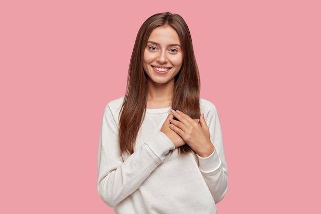 優しい笑顔で満足のいく寛大なブルネットの女性は、胸に両手のひらを保ちます 無料写真
