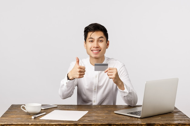 Satisfied good-looking asian office worker, manager sitting desk with documents, laptop and cup coffee, holding credit card, show thumbs-up and smiling, recommend buy online and use bank service Premium Photo