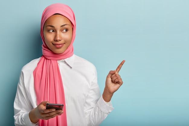 Довольная красивая женщина с темной кожей, держит мобильный телефон, болтает с подписчиками в социальных сетях, показывает указательным пальцем, демонстрирует свободное место для рекламного контента, носит шарф на голове Бесплатные Фотографии