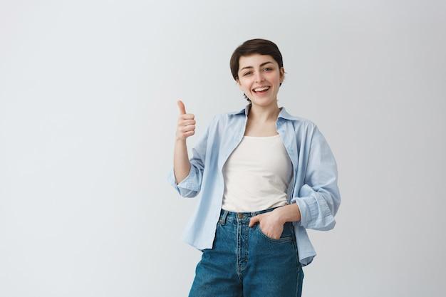 Удовлетворенная красивая женщина с короткими волосами, одобрительно показывая большие пальцы руки вверх, хвалит отличный выбор Бесплатные Фотографии