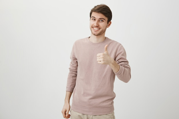 Satisfied handsome caucasian man showing thumbs-up Free Photo