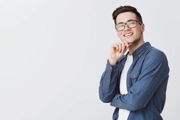 Довольный красивый парень в очках с довольным видом в правом верхнем углу и довольной улыбкой Бесплатные Фотографии