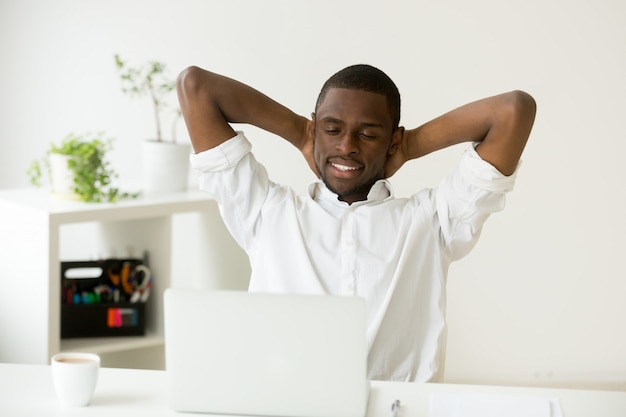 Satisfied happy african american man relaxing with coffee and laptop Free Photo