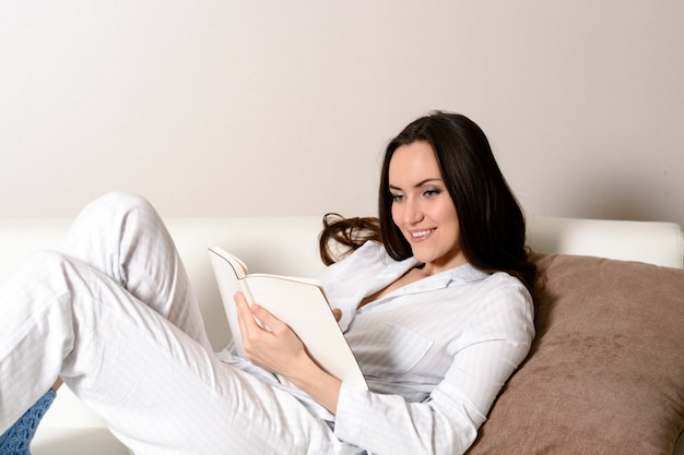 Satisfied and happy smiling girl lying on the sofa in the room and writes a journal of your dreams Premium Photo