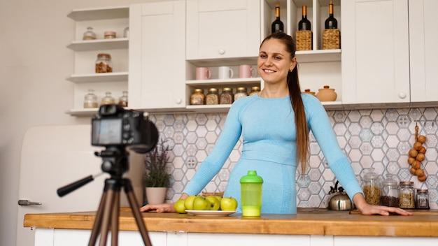 Довольная здоровая молодая девушка, стоя на кухне дома, записывает эпизод своего видеоблога о здоровой пище. женщина дружелюбная и улыбчивая Premium Фотографии
