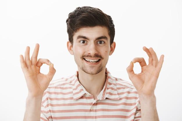 口ひげを持ち、指を上げ、大丈夫か大丈夫なジェスチャーを示し、素晴らしい提案を承認し、問題を解決して満足し、すべてをコントロールできる満足している魅力的な男性 無料写真