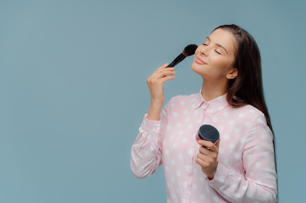 Satisfied lady applyes foundation with cosmetic brush Premium Photo
