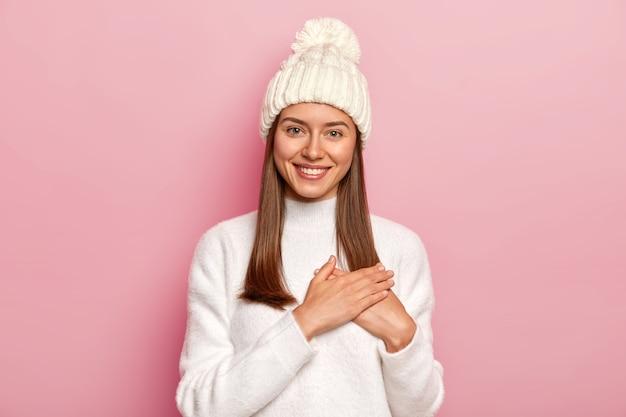 ストレートヘアで満足している素敵な女性、彼氏から心温まる言葉を受け取り、感謝のジェスチャーをし、ピンクの壁に隔離された快適な白いセーターと帽子をかぶっています 無料写真