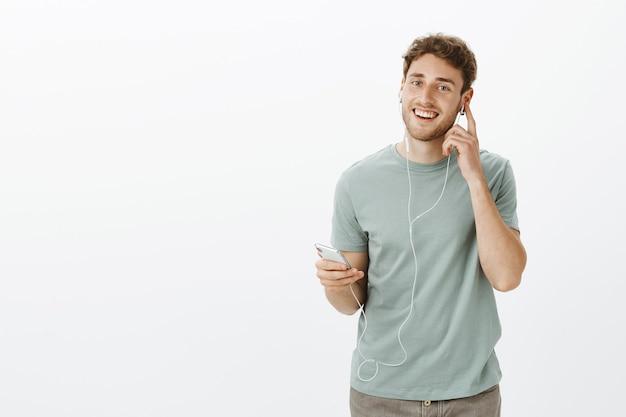 Modello maschio caucasico soddisfatto soddisfatto con setola, tenendo lo smartphone e toccando gli auricolari mentre si ascolta la musica e si gode un bel suono degli auricolari Foto Gratuite
