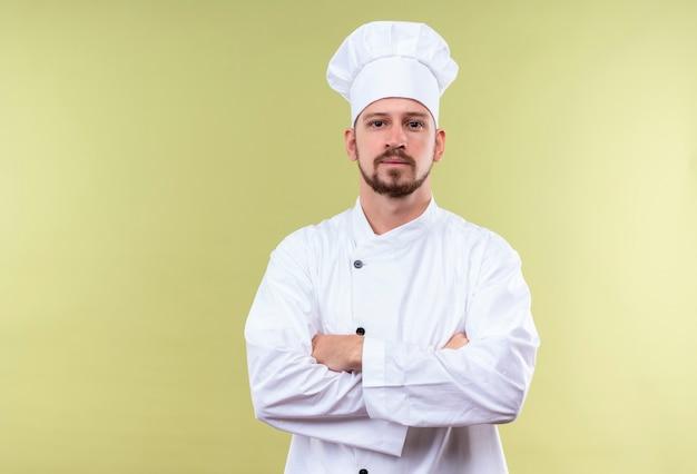 満足しているプロの男性シェフが白い制服を着て調理し、腕を組んで帽子を組んで緑の背景に自信を持って探して 無料写真