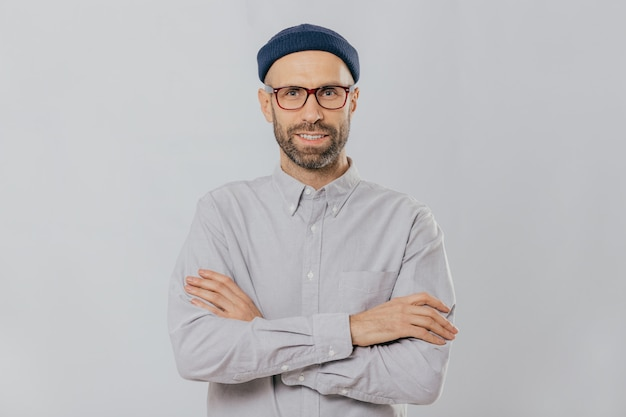 Satisfied self confident male designer wears stylish headgear, dressed in white shirt, keeps arms folded Premium Photo