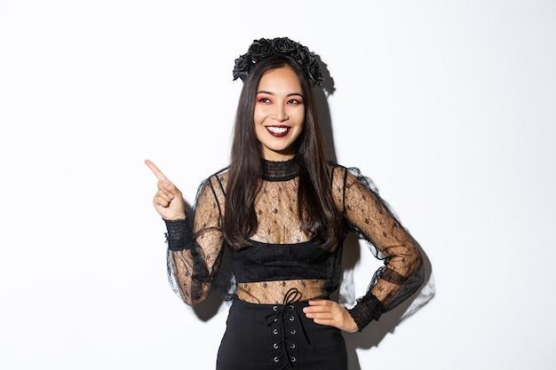 사악한 마녀 또는 할로윈을 축하하는 밴시 의상에 만족 된 웃는 아시아 여자, 기쁘게 찾고 손가락 왼쪽 상단 모서리를 가리키는, 프로모션 배너, 흰색 배경 표시. 무료 사진
