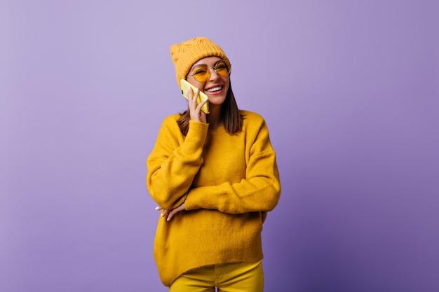 スマートフォンで親友と話しながら幸せな肩の長い髪の満足した女性。スタイリッシュな帽子と黄色の服を着た本物の笑顔の学生は、孤立した紫色のスナップポートレートを作りたいと思っています 無料写真