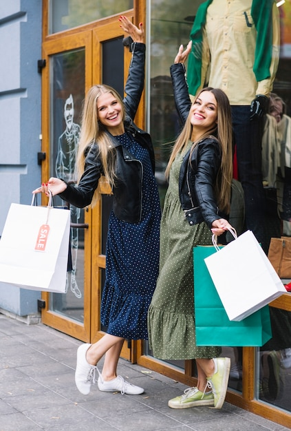 87863b055 Satisfied young women holding shopping bags posing in front of clothes  store Free Photo