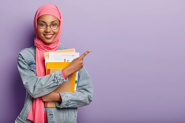 Satisified muslim college student with notepad and papers Free Photo