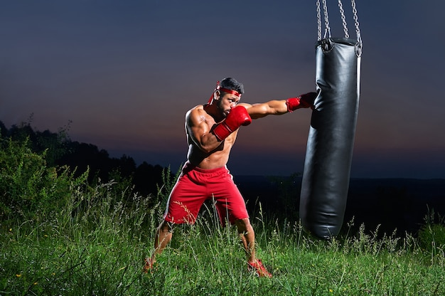 Saturated shot of a male boxer training with sandbag Premium Photo