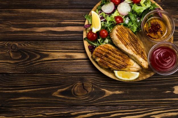 Salsa e spezie vicino insalata e pollo Foto Gratuite