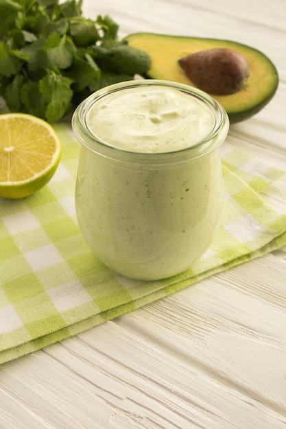 Соус с йогуртом, авокадо, лаймом и кинзой на белом деревянном фоне. расположение вертикальное. Premium Фотографии