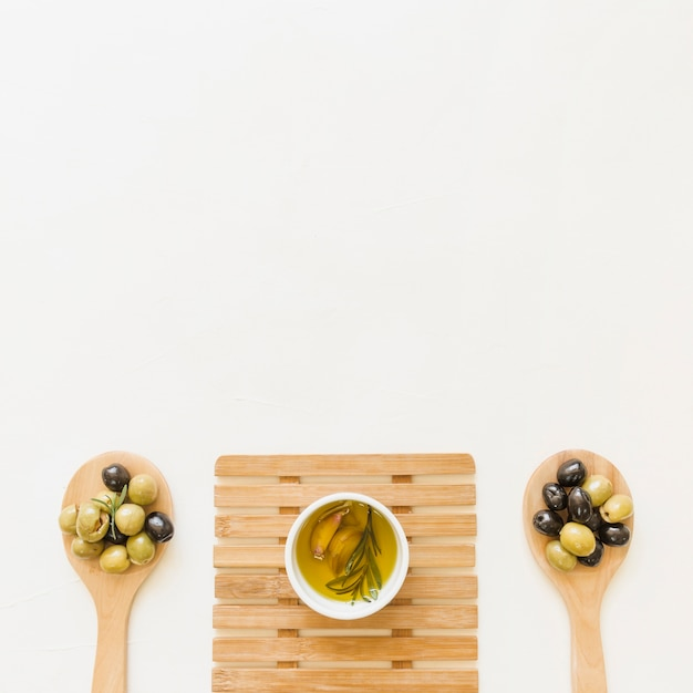 Sauceboat on hot pad with olives in spoons Free Photo