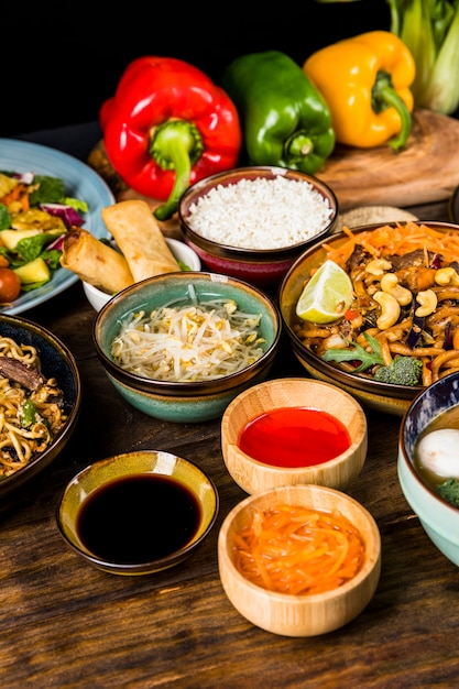 Sauces with traditional thai food with bell peppers on table Free Photo