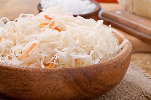 Sauerkraut with carrot in wooden bowl Free Photo