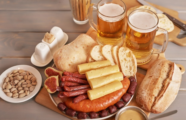 Sausage and cheese slices with light beer and pistachios for oktoberfest Premium Photo