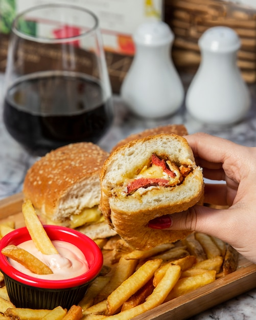 Sausage hamburger with fried sausage, served with fries, and mayonnaise Free Photo