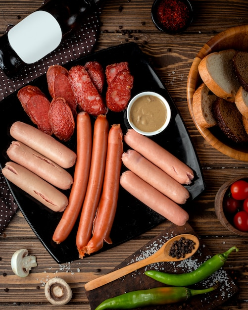 Sausage selection served with mustard Free Photo