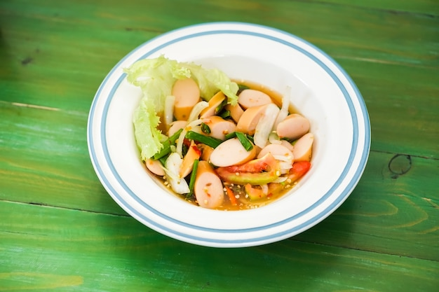 Sausage spicy salad in a bowl put on the green table. Premium Photo