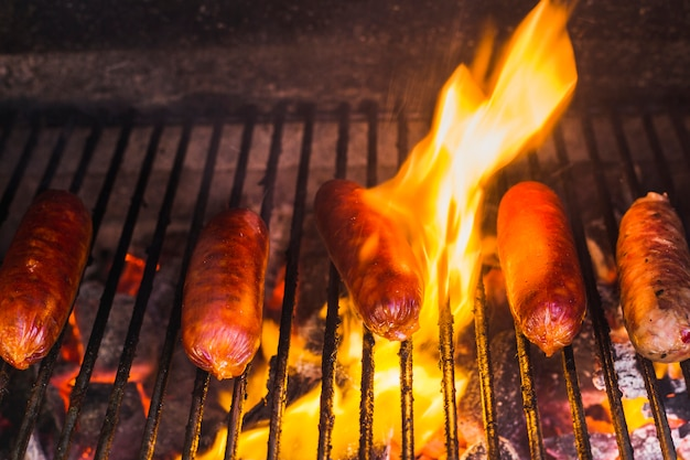 Sausages grilling over the hot glowing coals in a portable barbecue Free Photo