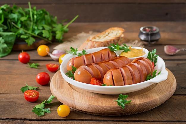 Колбаски на гриле сковороду на деревянном столе Бесплатные Фотографии