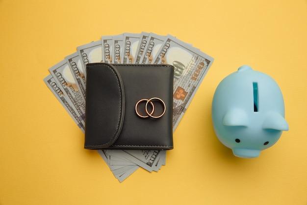 新婚旅行、結婚式の旅行のためにお金を節約してください。お金で財布にリングが付いている貯金箱 Premium写真