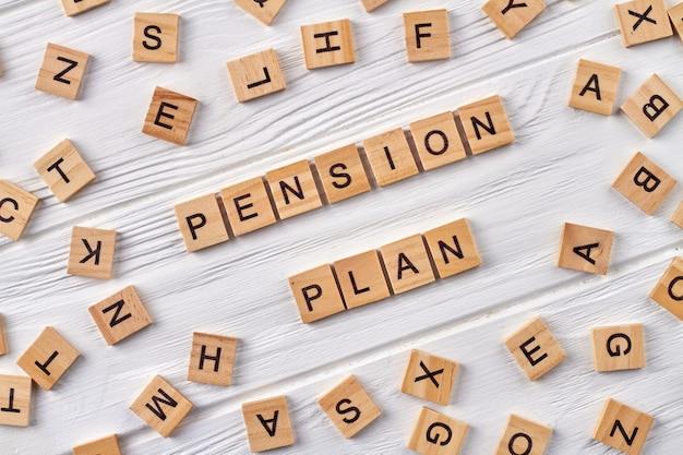 Накопление денег как пенсионный план. деревянные кубики с буквами на деревянном полу. Premium Фотографии