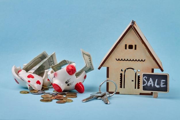 壊れた貯金箱で新しい家のコンセプトのためにお金を節約 Premium写真