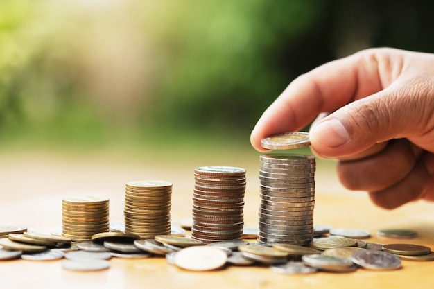 Saving money hand putting coins on stack on table with sunshine. concept finance and accounting Premium Photo