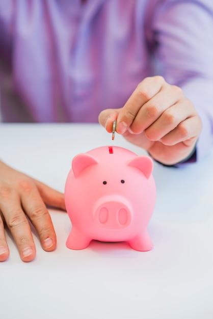 Saving money in piggy bank, close up Free Photo