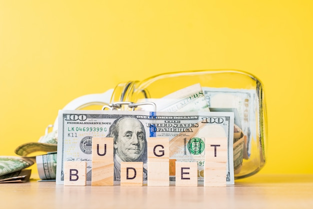 Saving money and planning budget concept dollar bills in glass saving bank and word budget Premium Photo