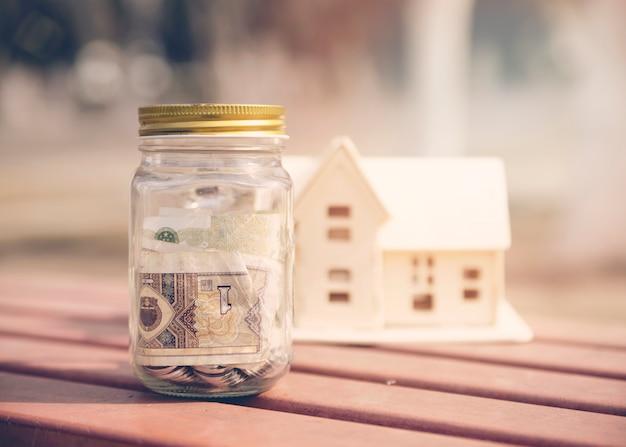 Savings jar with house miniature Free Photo