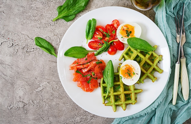 Savory waffles with spinach and egg, tomato, salmon in white plate. Premium Photo