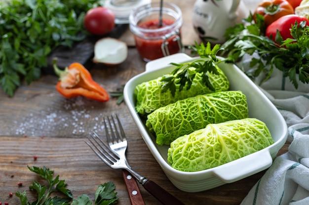 Савойские голубцы, фаршированные мясом, рисом и овощами на деревенском столе. Premium Фотографии