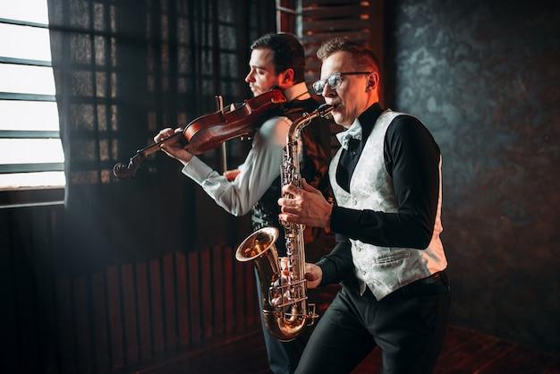 Дуэт саксофона и скрипача играет классическую мелодию Premium Фотографии