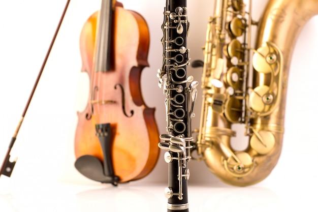 Саксофон тенор саксофон скрипка и кларнет в белом Premium Фотографии