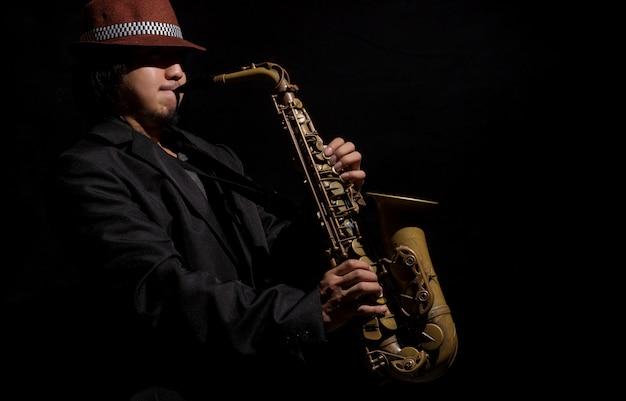 A saxophone player in a dark background Premium Photo